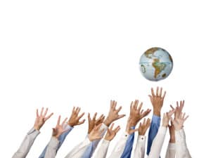 multi ethnic hands reaching for globe ball
